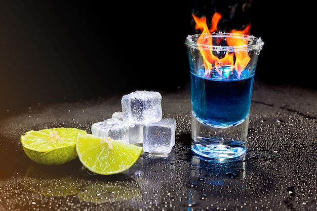 Cocktailblau, das im schnapsglas mit salz und limette, eiswürfel auf schwarzer oberfläche brennt.