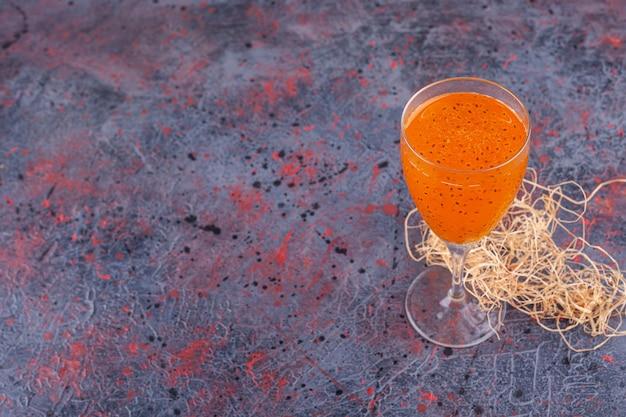 Cocktailglas frischer saft mit basilikumsamen auf marmor.