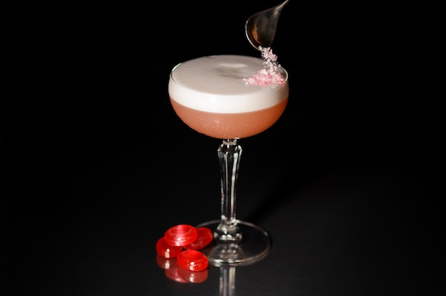 Cocktailglas mit dem süßen alkoholischen getränk verziert mit süßigkeiten