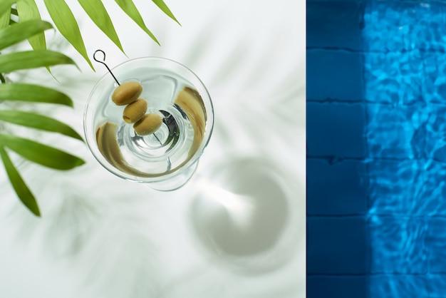Cocktailglas mit martini und oliven am pool erfrischungsgetränke an einem heißen sommertag