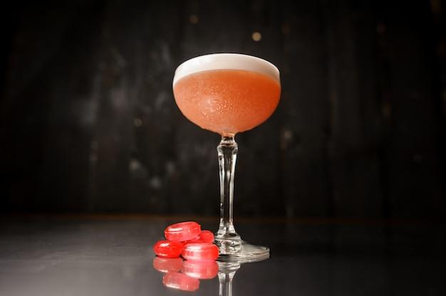 Cocktailglas mit süßem alkoholischem getränk diente mit rosa süßigkeiten