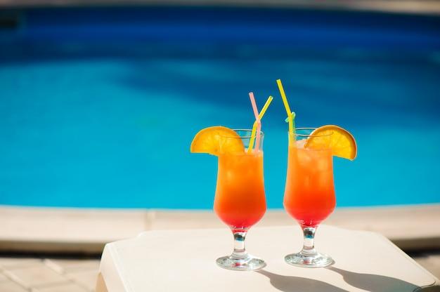 Cocktails auf dem hintergrund des pools.