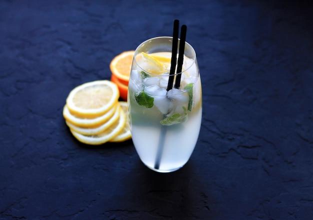 Cocktails mit eis in hohen gläsern mit frucht- und cocktailgefäßen auf einem dunklen hintergrund