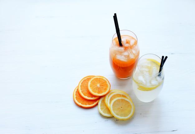 Cocktails mit eis in hohen gläsern mit frucht- und cocktailgefäßen auf einem hellen hintergrund