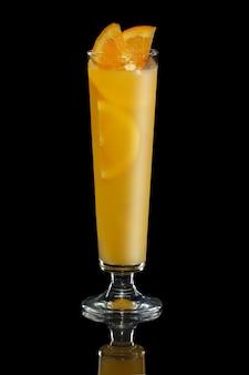 Cocktailtequila mit dem orangensaft lokalisiert auf schwarzem