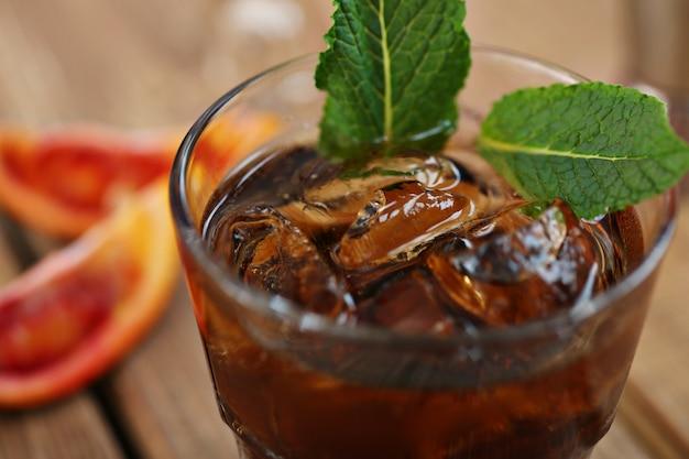 Cocktailwhiskykolabaum mit eis in einem glas. auf einem holzbrett sind fragmente von früchten. foto mit schärfentiefe.