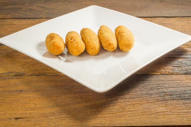 Codfish-stückchen oder kabeljau backt, ein traditioneller aperitif in portugal auf weißem hintergrund zusammen