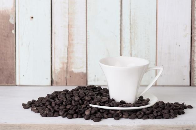 Cofee cup und bohnen auf retro- hölzernem ackground