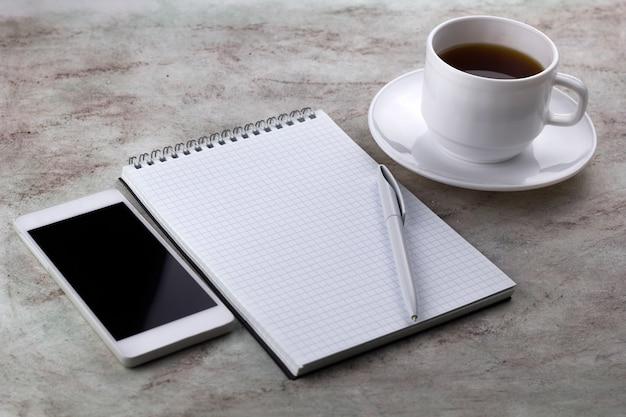 Coffe cup, cel-telefon und notizbuch auf einem marmorhintergrund
