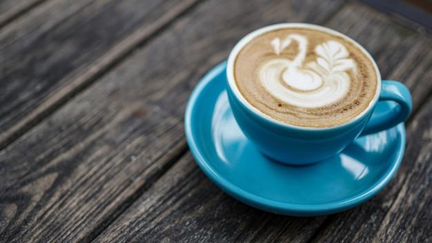Coffeelatte mit blauer tasse und gans ziehen in belag