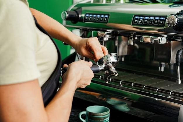 Coffeeshop-arbeiter der frau, der kaffee auf professioneller kaffeemaschine vorbereitet