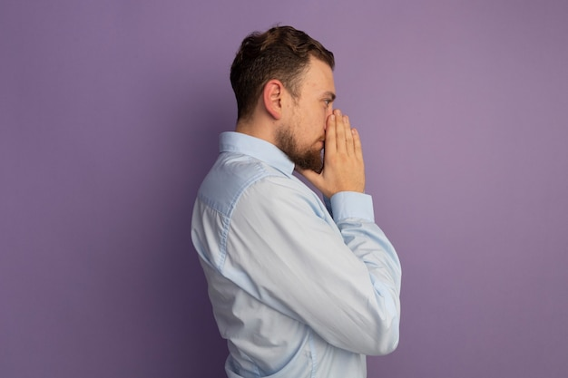 Cofident gutaussehender blonder mann steht seitlich und hält hände zusammen nahe nase lokalisiert auf lila wand