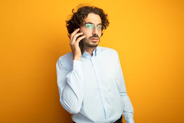 Cofident junger hübscher kaukasischer mann, der brillen spricht, die am telefon sprechen kamera betrachten, die auf orange hintergrund mit kopienraum lokalisiert wird