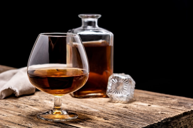 Cognac-getränk auf holztisch und schwarzgrund