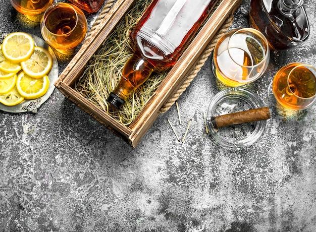 Cognac hintergrund. eine flasche cognac mit zitronenschnitzen und einer zigarre. auf einem rustikalen hintergrund.