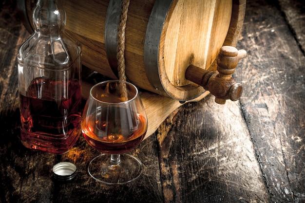 Cognac in einem fass mit einem glas. auf einem hölzernen hintergrund.