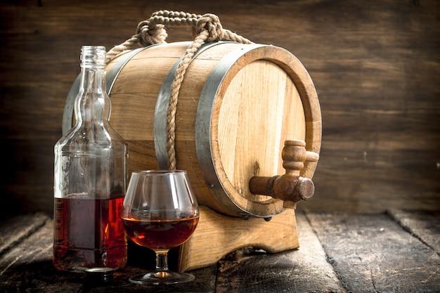 Cognac in einem fass mit einem glas