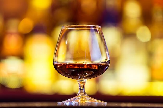 Cognac in einem glas auf hellen lichtern. traditionelles französisches getränk.
