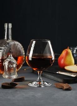 Cognac in einem glas mit schokolade und birne