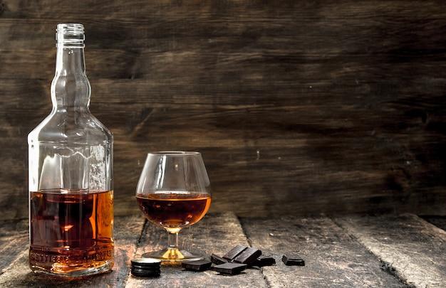 Cognac mit bitterschokolade. auf einem hölzernen hintergrund.