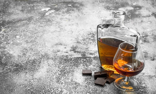 Cognac mit bitterschokolade. auf einem rustikalen hintergrund.