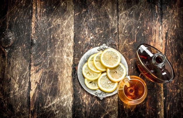 Cognac mit zitronenschnitzen. auf einem hölzernen hintergrund.