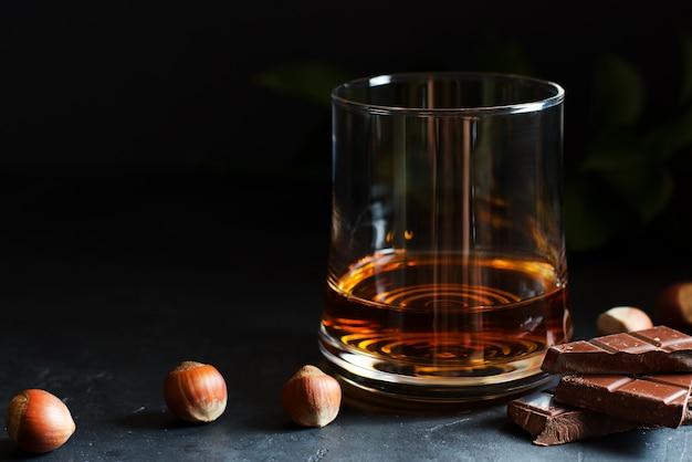 Cognac oder rum oder bourbon in einem glas. schokoladenstücke und haselnüsse.