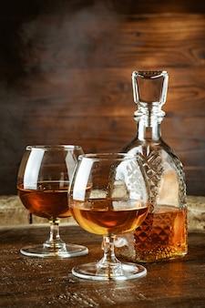 Cognac oder whiskey in gläsern auf rustikalem backgrpund
