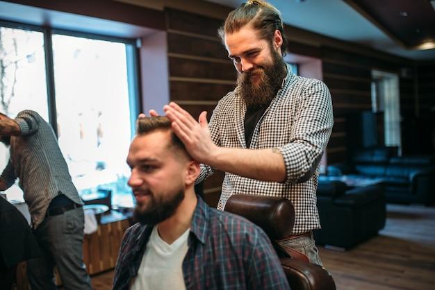 Coiffeur stapelt frisur nach dem haarschnitt
