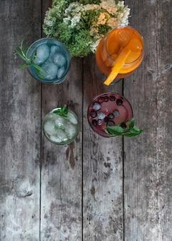Coktail gin tonic, mojito und aperol spritz mit minze, eis, limette, beeren, grapefruit und orange auf dem holzhintergrund.