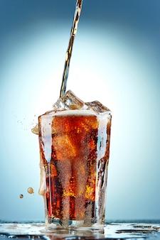 Cola gießt in ein glas