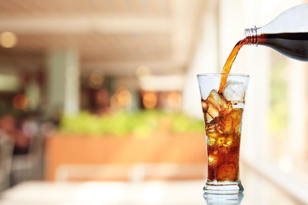 Cola gießt in glas