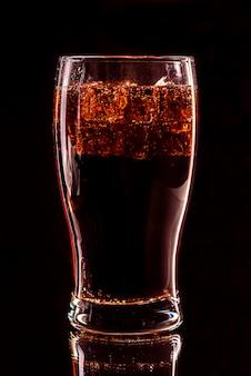 Cola-glas mit eiswürfeln und tröpfchen, isoliert und mit schnittpfad