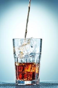 Cola in ein glas gießen