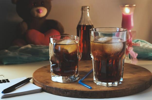 Cola in einem glas mit eis auf dem hintergrund einer brennenden kerze und eines teddybären.