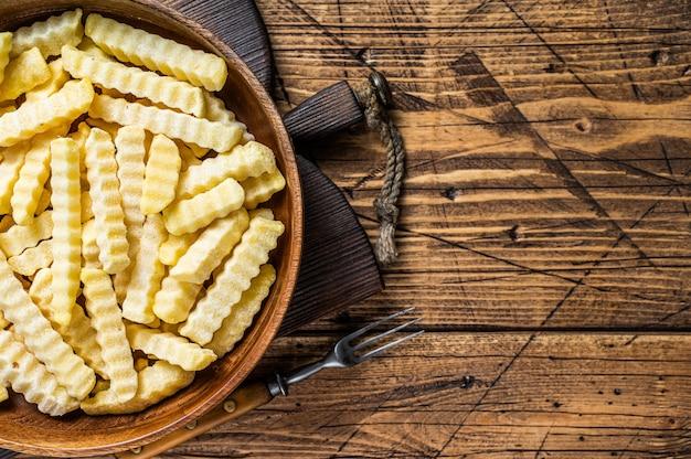 Cold frozen crinkle-ofen pommes-frites-kartoffel-sticks in einer holzplatte. hölzerner hintergrund. ansicht von oben. platz kopieren.