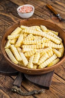 Cold frozen crinkle-ofen pommes-frites-kartoffel-sticks in einer holzplatte. hölzerner hintergrund. ansicht von oben.
