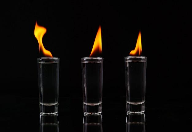 Collage hot chili pfeffer in einem schnapsglas mit einem feuer auf schwarz