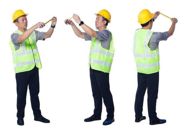 Collage in voller länge figur der 50er 60er jahre asiatischer älterer mann ingenieur tragen sicherheitswesten-schutzhelmwerkzeuge. älterer mann misst die entfernung mit maßband über weißem hintergrund isoliert