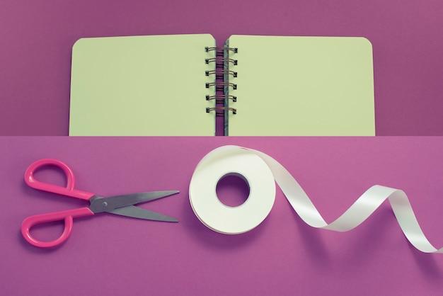Collage scissors und rolle des bandes im weiß auf einem purpurroten hintergrund