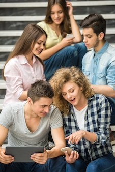 College-freunde beobachten bilder am telefon in der pause.