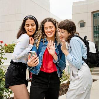 College-mädchen videoanrufe mit freunden auf dem campus
