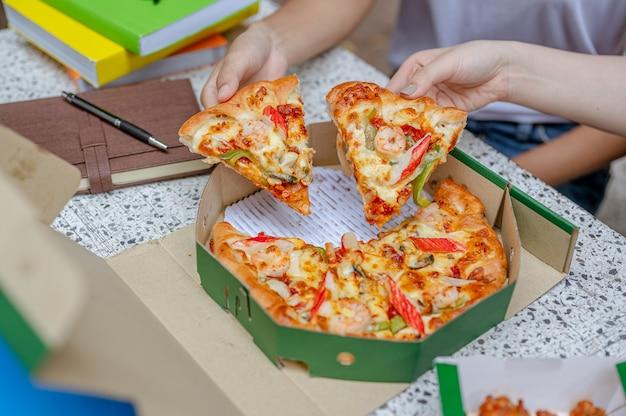 College-student, der pizza isst, während er nachhilfe leistet und an einem projekt arbeitet universitäts-wissensbuch
