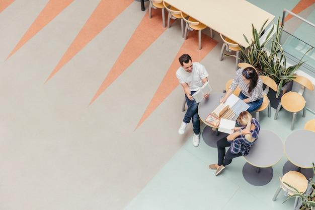 College-studenten, die mit büchern sitzen