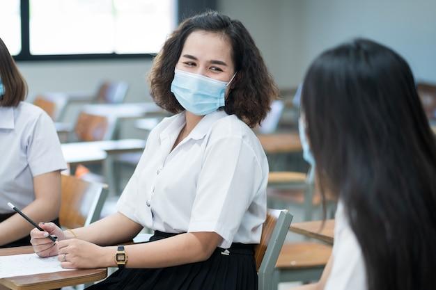 College-studenten im teenageralter schreiben im klassenzimmer auf prüfungspapier antwortbogen