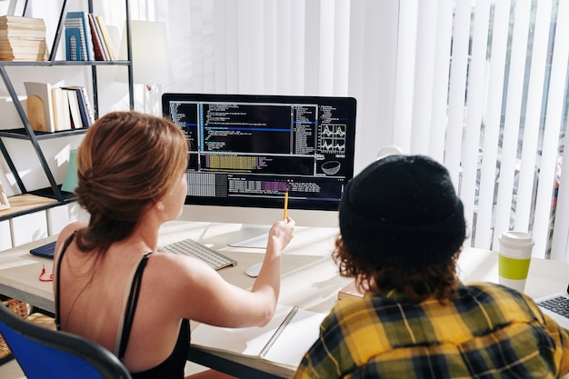 College-studenten schauen sich zu hause ein webinar über informatik an und diskutieren den programmcode auf dem computerbildschirm