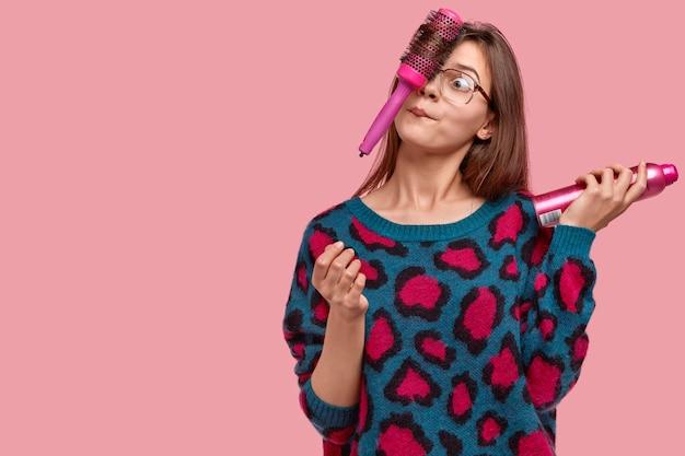 Comic frau töricht, während haare kämmen, hält haarbürste im gesicht, hat lustigen gesichtsausdruck, spray zum fixieren getragen