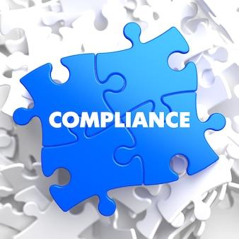 Compliance auf blue puzzle auf weißem hintergrund.