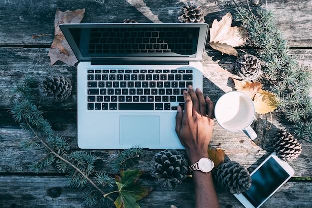 Computer auf einem holztisch mit dem kaffee und kiefern im freien