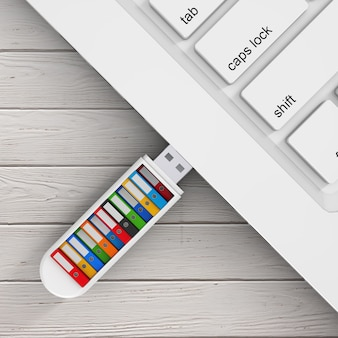 Computer-business-konzept. bunte office-ordner in usb-flash-laufwerk mit laptop auf einem holztisch verbunden. 3d-rendering